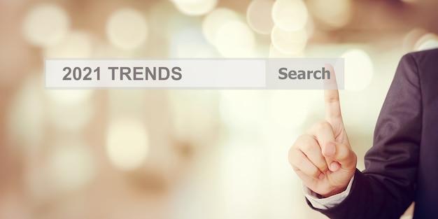 Main d'homme d'affaires touchant la barre de recherche des tendances 2021 sur fond de bureau flou