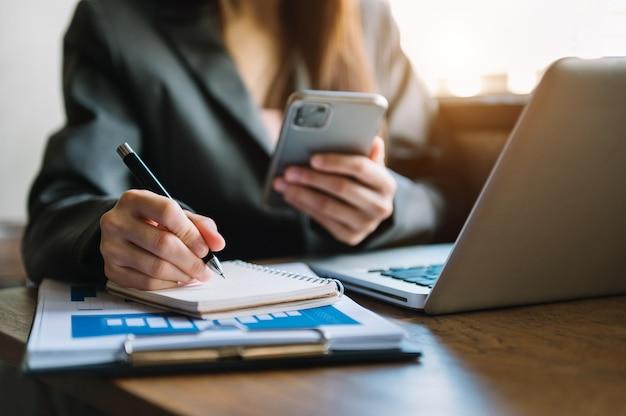 Main d'homme d'affaires travaillant avec un nouvel ordinateur moderne et écrivant sur le diagramme de stratégie du bloc-notes comme concept lumière du matin