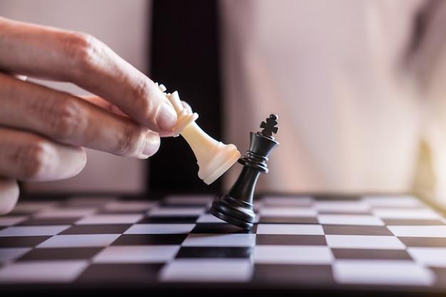 Main d'homme d'affaires utiliser roi pièce d'échecs blanc jeu de jeu pour renverser renverser l'opposition