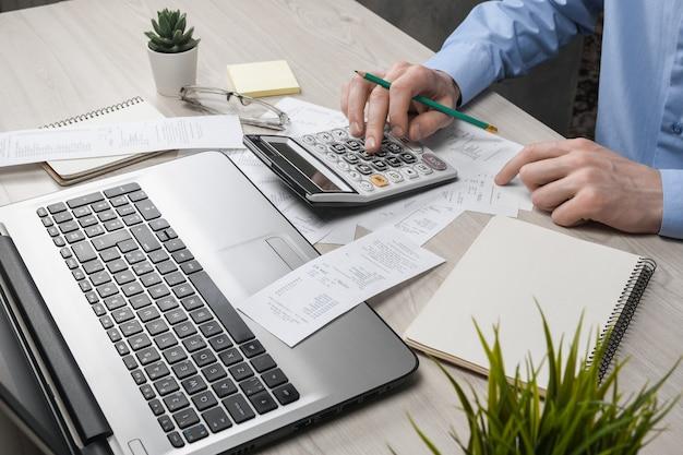 Main de l'homme à l'aide de la calculatrice et de l'écriture prendre note avec calculer le coût et les taxes au bureau à domicile. homme d'affaires faisant de la paperasse sur le lieu de travail