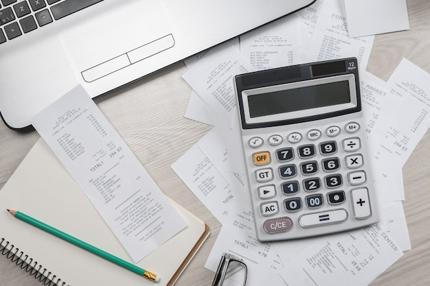 Main de l'homme à l'aide de la calculatrice et de l'écriture prendre note avec calculer le coût et les taxes au bureau à domicile