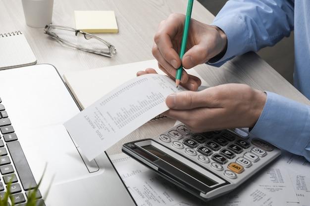 Main de l'homme à l'aide de la calculatrice et de l'écriture prendre note avec calculer le coût et les taxes