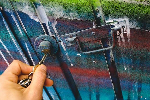 La main de l'homme à l'aide d'une clé pour ouvrir la serrure d'une porte d'un garage abandonné.