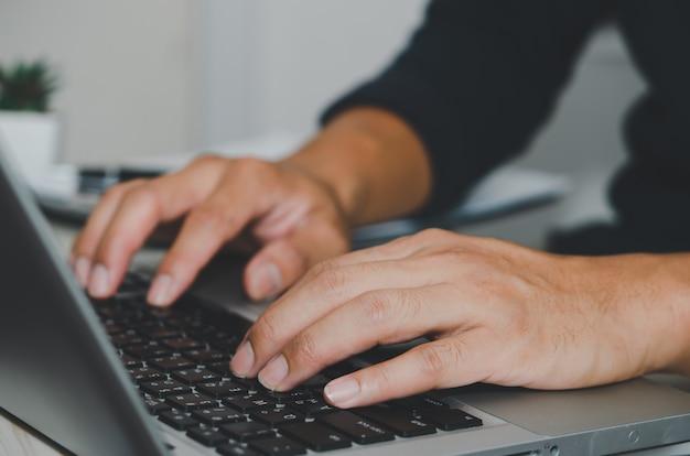 Main de l'homme à l'aide du clavier de l'ordinateur portable. recherche sur internet, informations, réseaux sociaux. entreprises commercialisant des achats en ligne.