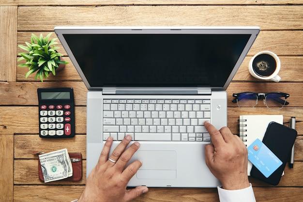 Main d'homme à l'aide d'un ordinateur portable