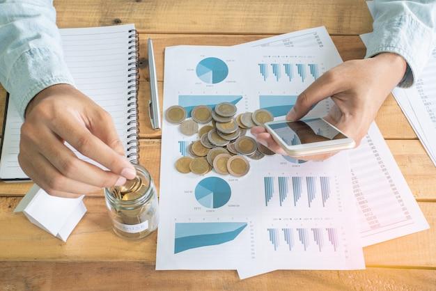 Main d'homme à l'aide de smartphone et de mettre des pièces de monnaie dans le verre sur une table de travail en bois avec un tas de pièces de monnaie, carnet de notes, stylo et mini maison blanche modèle - investissement, affaires, finance et banque