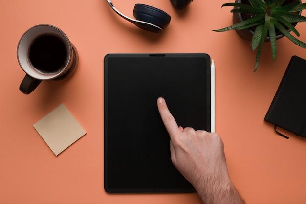 Une main d'homme à l'aide d'une tablette numérique maquette