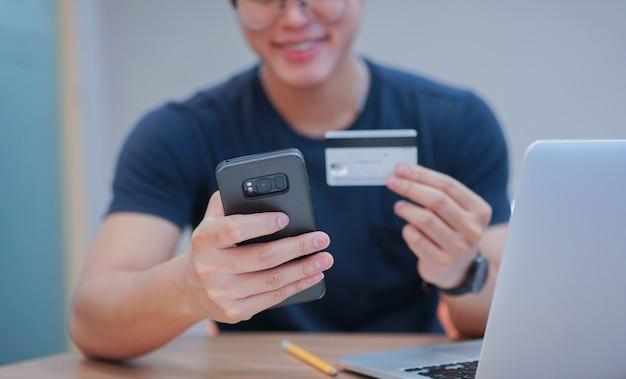Main d'homme à l'aide de téléphone portable pour payer en ligne avec carte de crédit