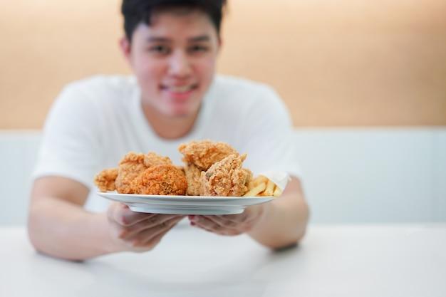 Main d'homme aisan et repas de poulet frit pour manger au restaurant