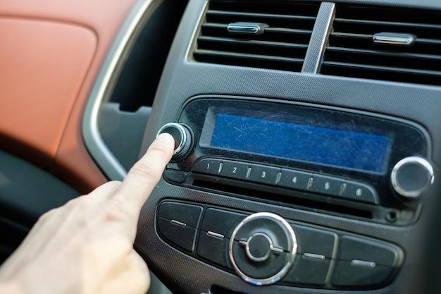 Main d'homme ajustant le contrôle audio de voiture de bouton de presse