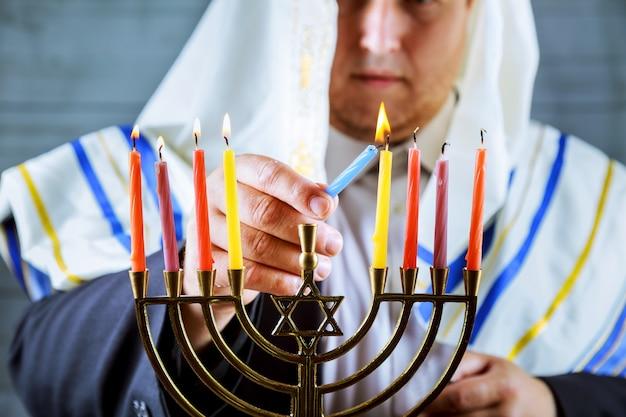 Main d'homme allumant des bougies dans la menorah sur une table servie pour hanoukka