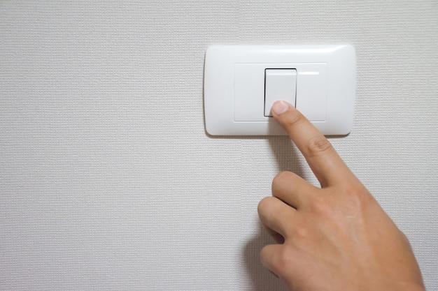La main de l'homme allume ou éteint l'interrupteur d'éclairage électrique