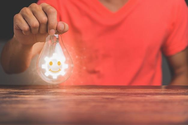 Main d'homme avec ampoule et il y a une icône d'engrenage