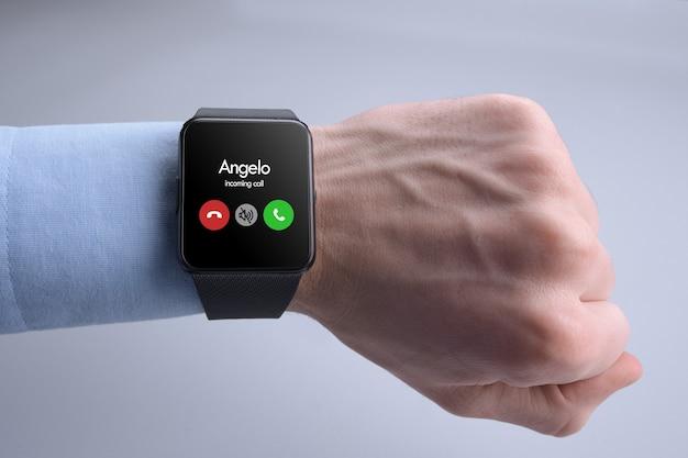 Main de l'homme avec appel entrant smartwatch considérant prendre un appel ou non.