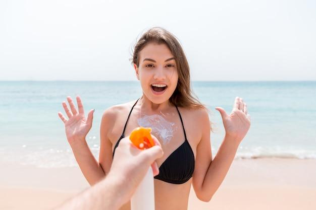 La main de l'homme applique soudainement une lotion solaire sur la poitrine d'une femme surprise