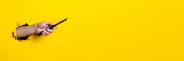 La main de l'homme appuie sur le bouton de la télécommande du téléviseur sur un fond jaune vif