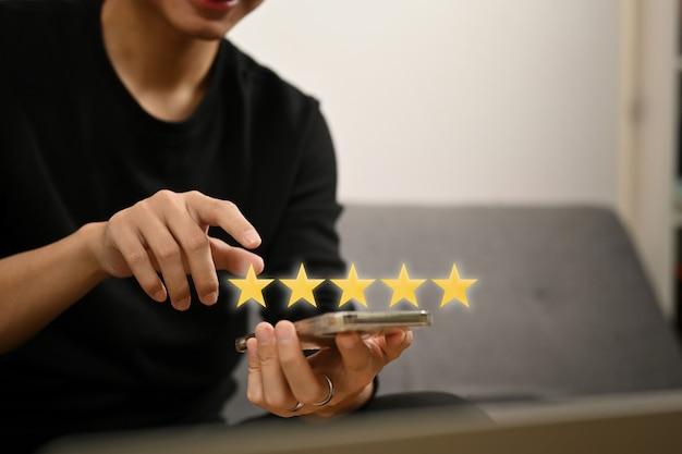 Main de l'homme appuyant sur l'écran du smartphone avec cinq étoiles d'or, donnant des commentaires positifs.