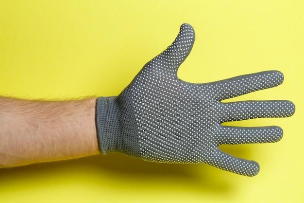 Main d'un homme, artisan, jardinier dans un gant gris sur fond jaune
