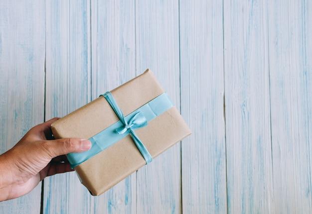 Main d'homme asiatique avec boîte-cadeau en papier brun avec espace copie, vue du haut