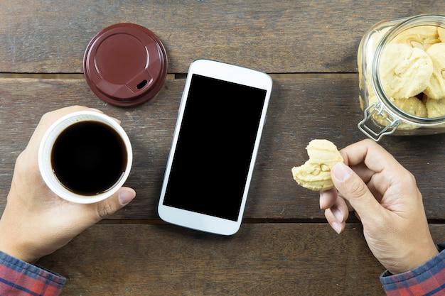 Main d'homme asiatique tenant des biscuits et une tasse de café noir sur fond de table en bois