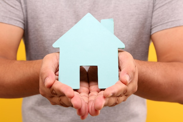 Main de l'homme asiatique tenir la forme de la maison de papier bleu