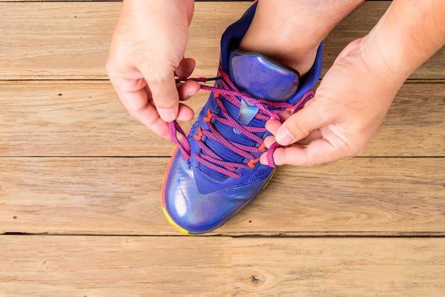 Main de l'homme attachant des lacets de chaussures de basket avant de jouer au basket sur planche de bois