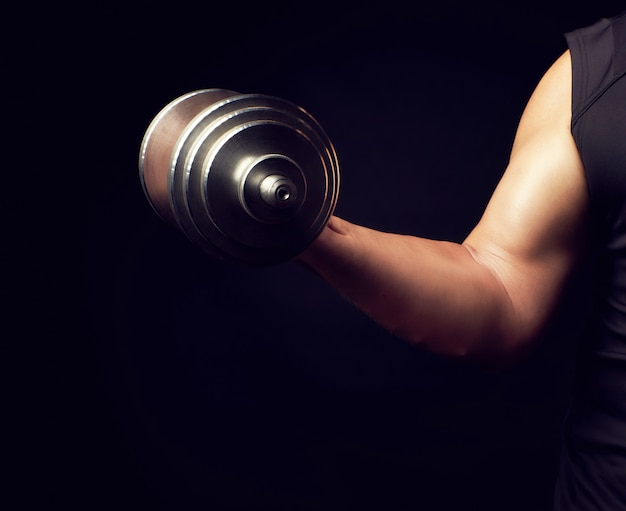 Main d'un homme au grand biceps tient un haltère en acier