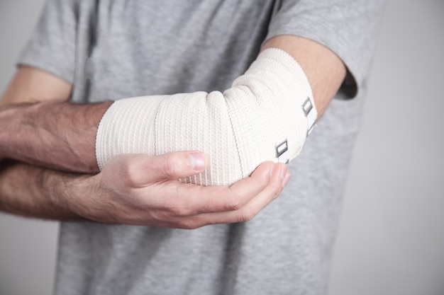Main de l'homme avec un bandage élastique sur le coude.