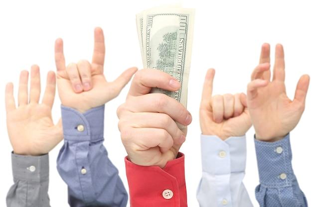 La main de l'homme avec des billets d'un dollar sur l'espace des autres mains levées. affaires et finances. gagnant du concours. recherche d'emploi