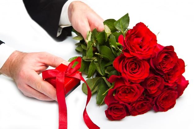 Main d'homme avec bouquet de roses rouges et coffret cadeau