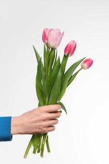 La main d'un homme avec un bouquet de tulipes sur fond clair.