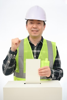 La main de l'homme sur le bulletin de vote dans l'urne.
