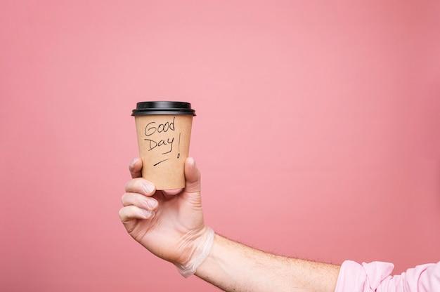 La main de l'homme avec un café dans une tasse en carton recyclable