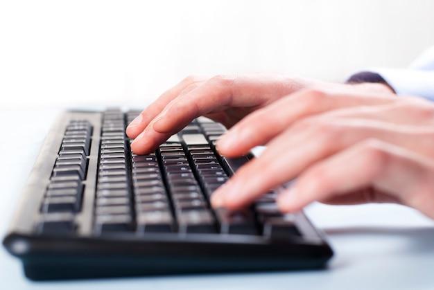 Main de l'homme sur le clavier de l'ordinateur main de femme sur le clavier en tapant