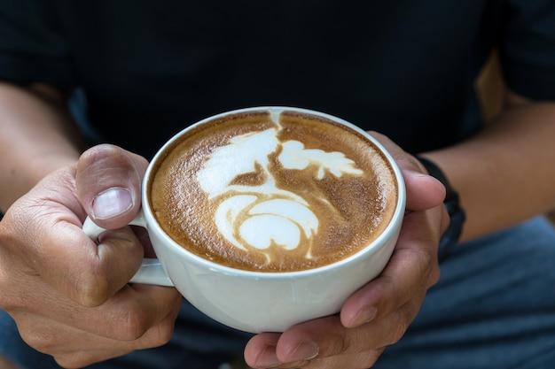 Main de l'homme closeup tenant la tasse de café avec concept de latte art, art et boisson