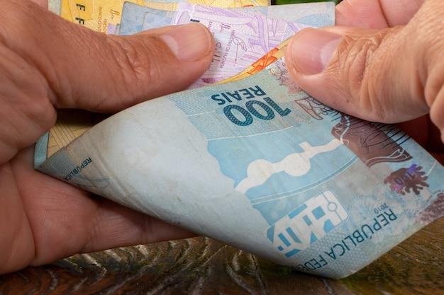 Main d'homme comptant l'argent brésilien