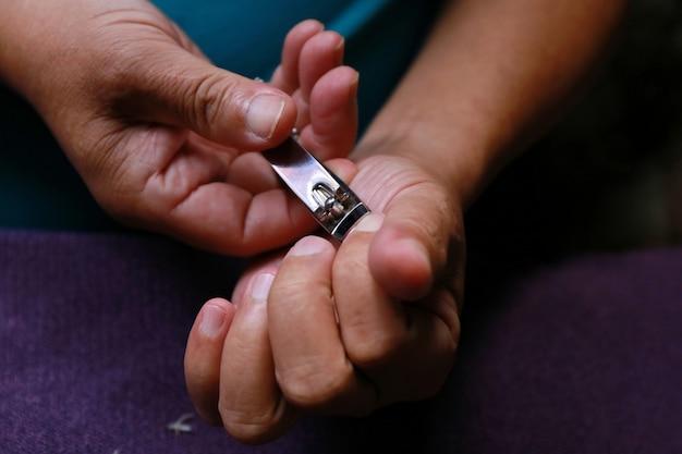 Main d'homme coupant les ongles