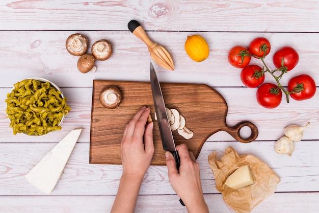 Main de l'homme coupe champignon pour faire de délicieuses pâtes sur une surface en bois