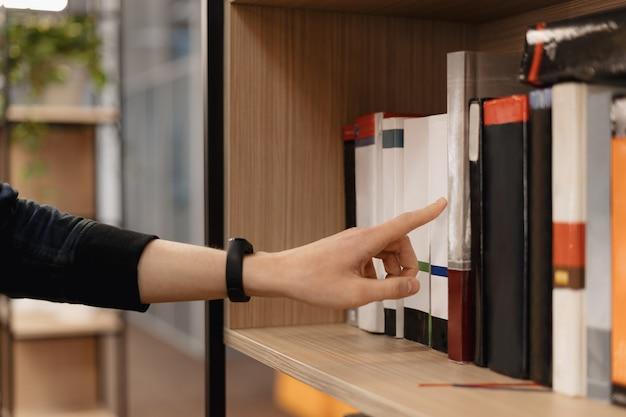 La main de l'homme cueillait des livres sur l'étagère