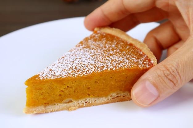 La main de l'homme cueillant une tranche de tarte à la citrouille alléchante dans une assiette blanche