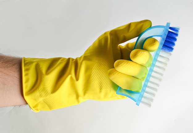 La main d'un homme dans un gant en latex jaune tient une brosse en plastique. concept de nettoyage