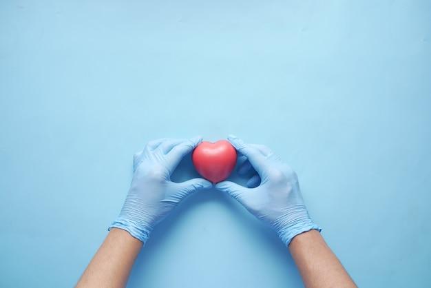 Main d'homme dans des gants de protection tenant un coeur rouge sur bleu