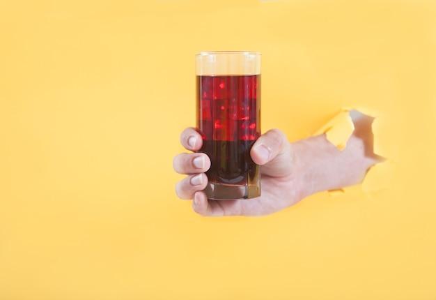 La main d'un homme dans un trou tient un verre de jus de cerise avec de la glace sur un fond jaune