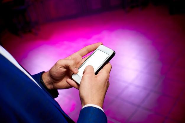 La main de l'homme dans une veste bleue tenant un téléphone avec un écran blanc