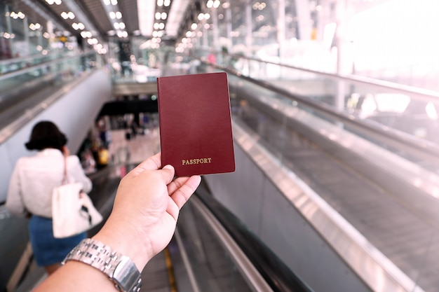 Main de l'homme détenteur d'un passeport à l'aéroport, ton rose en plastique.