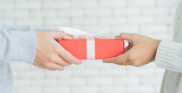 Main d'homme donnant une boîte cadeau rouge à une femme