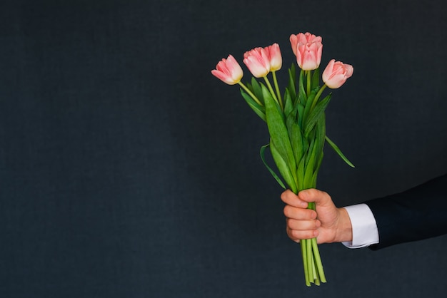 Main d'homme donnant un bouquet de tulipes roses