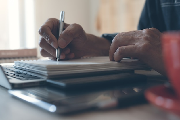 Main de l'homme écrit sur un cahier de papier et travaillant sur un ordinateur portable au bureau