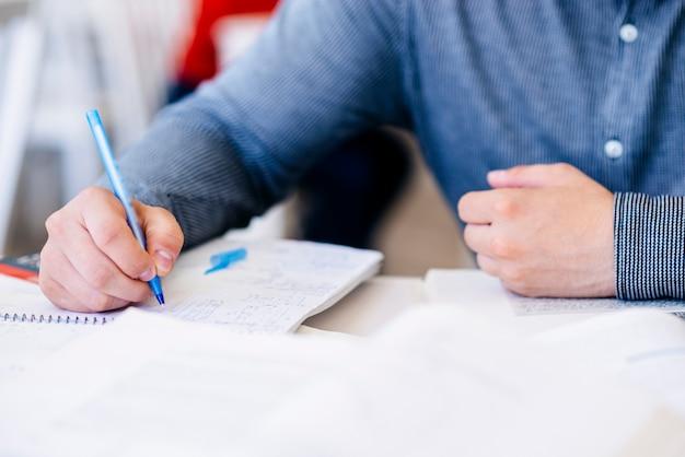 Main de l'homme écrit dans le cahier