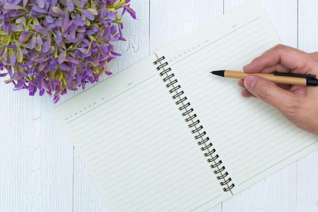 Main de l'homme écrit sur une page vierge de papier de cahier avec stylo, fournitures de bureau, vue de dessus.